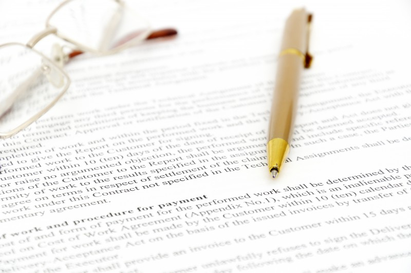 Contract with glasses and pen ready to be signed ** Note: Shallow depth of field